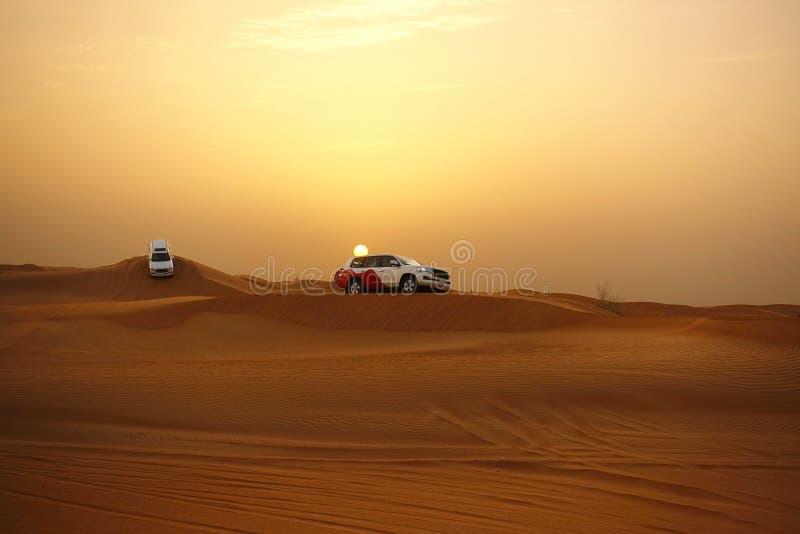 Aventúrese el safari del desierto en las dunas de arena con de los vehículos de camino en la puesta del sol foto de archivo libre de regalías