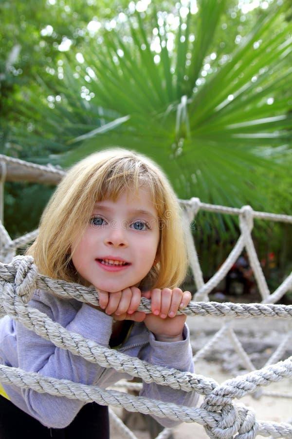 Aventúrese a la niña en el puente de cuerda del parque de la selva fotos de archivo