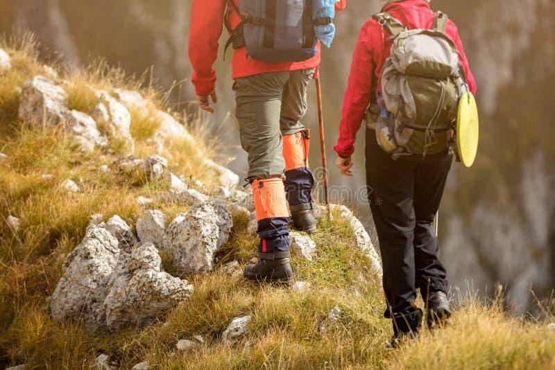 Aventúrese, viaje, turismo, alza y concepto de la gente - par sonriente que camina con las mochilas al aire libre imágenes de archivo libres de regalías