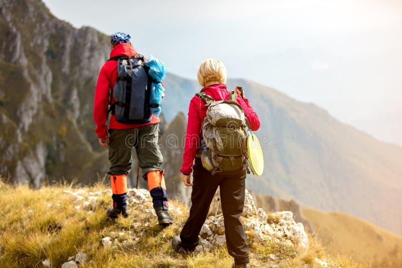 Aventúrese, viaje, turismo, alza y concepto de la gente - par sonriente que camina con las mochilas al aire libre fotos de archivo libres de regalías