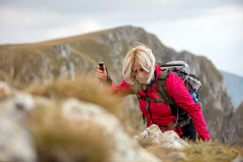 Aventúrese, viaje, turismo, alza y concepto de la gente - par sonriente que camina con las mochilas al aire libre imagen de archivo