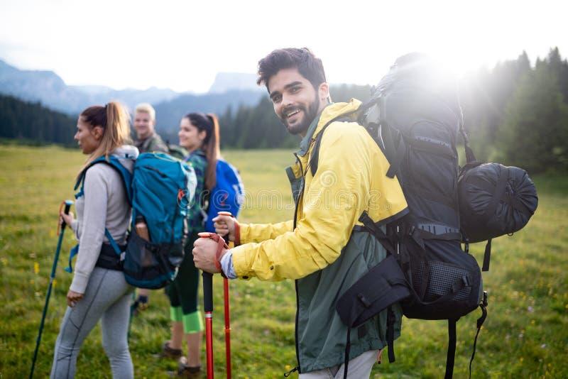 Aventúrese, viaje, turismo, alza y el concepto de la gente - grupo de amigos sonrientes con las mochilas y el mapa al aire libre fotografía de archivo libre de regalías