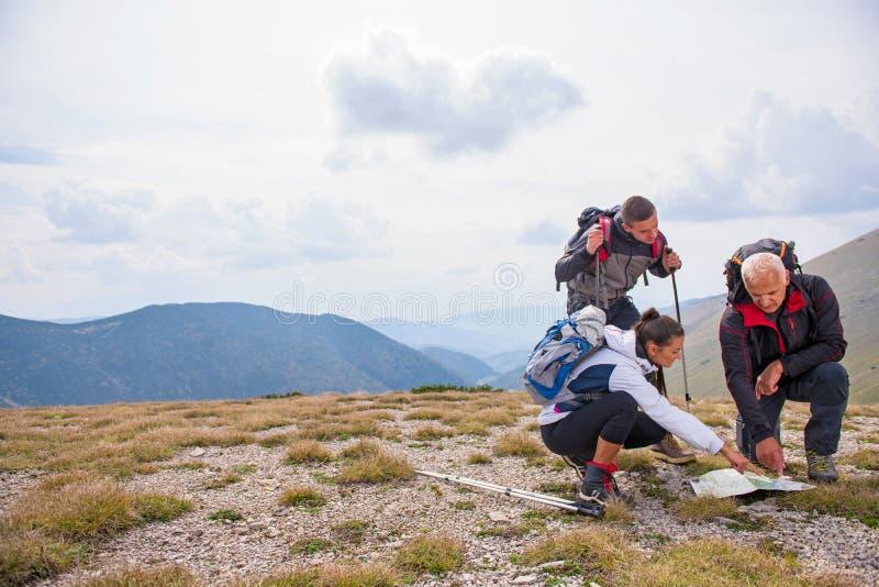 Aventúrese, viaje, turismo, alza y el concepto de la gente - grupo de amigos sonrientes con las mochilas y el mapa al aire libre fotografía de archivo