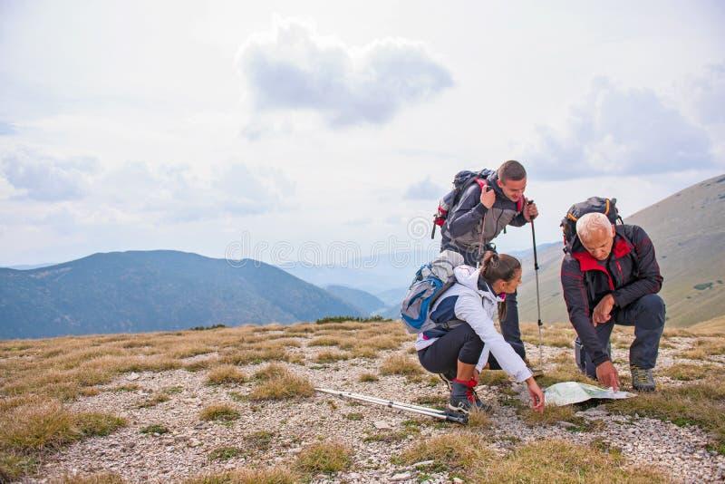 Aventúrese, viaje, turismo, alza y el concepto de la gente - grupo de amigos sonrientes con las mochilas y el mapa al aire libre imágenes de archivo libres de regalías