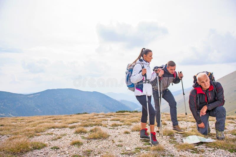 Aventúrese, viaje, turismo, alza y el concepto de la gente - grupo de amigos sonrientes con las mochilas y el mapa al aire libre imagen de archivo libre de regalías