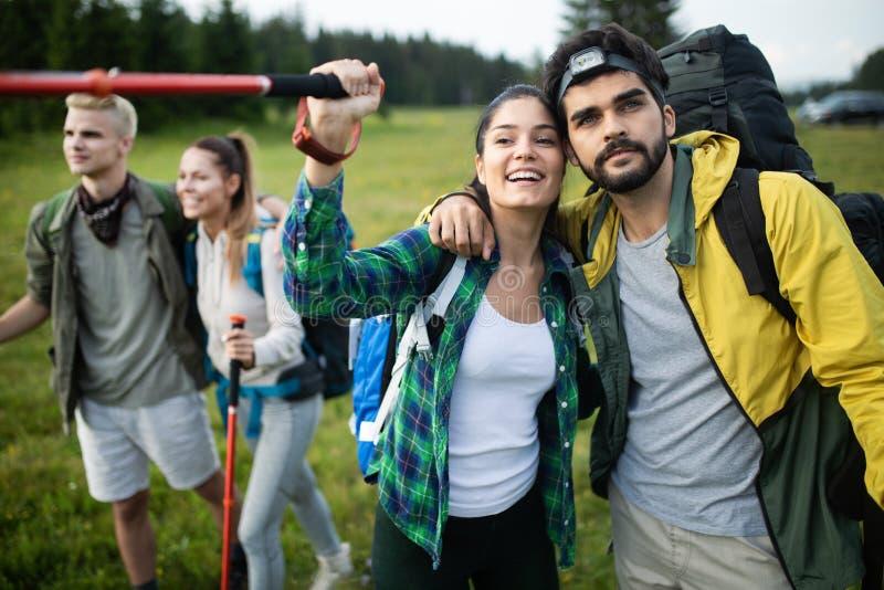 Avent?rese, viaje, turismo, alza y el concepto de la gente - grupo de amigos sonrientes con las mochilas y el mapa al aire libre imagen de archivo