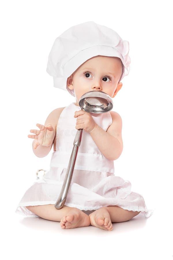 Avental do retrato emocional do bebê do cozinheiro e chapéu vestindo do cozinheiro chefe com a concha do metal, isolada em um fun fotos de stock