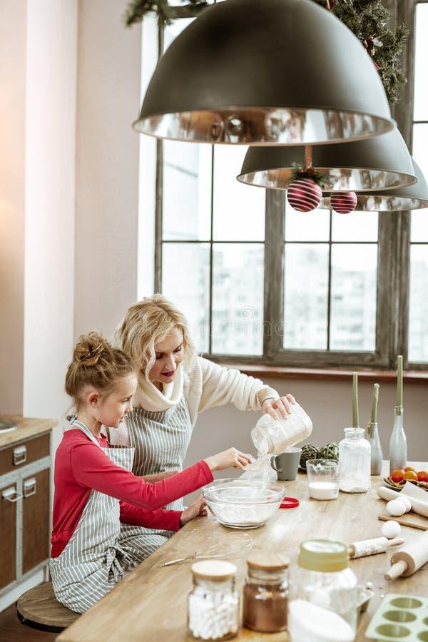 Avental listrado vestindo da mãe e da filha e cozimento na mesa de cozinha de madeira fotos de stock