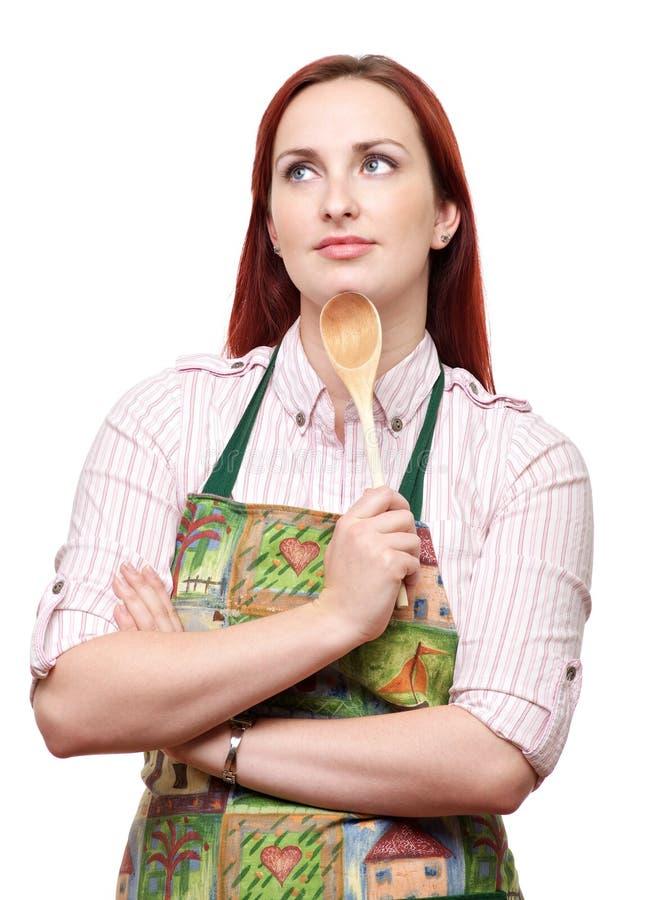 Avental vestindo da mulher, com uma colher de madeira fotografia de stock royalty free