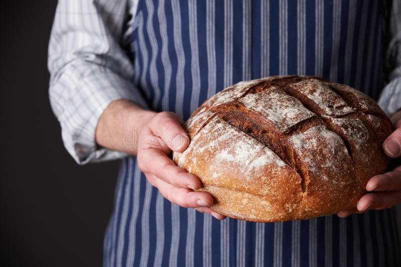 Avental vestindo do homem que guarda o naco de pão recentemente cozido foto de stock royalty free