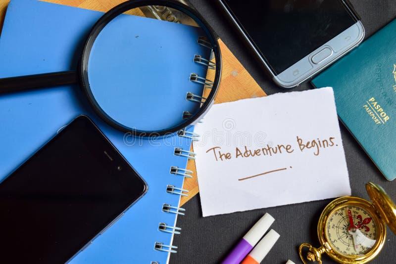 A aventura Begins escrito no papel passaporte, lupa, compasso, Smartphone foto de stock