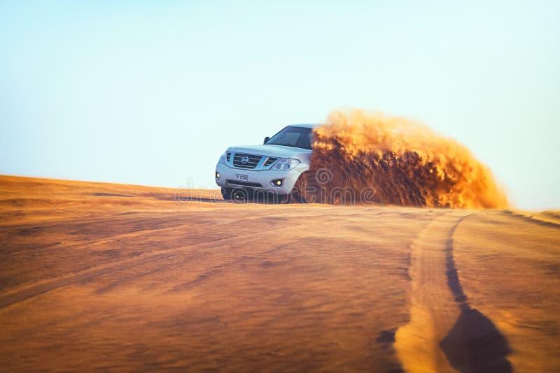 Aventura campo a través con Nissan Patrol SUV en desierto árabe en la puesta del sol Vehículo campo a través que golpea a través  fotografía de archivo libre de regalías