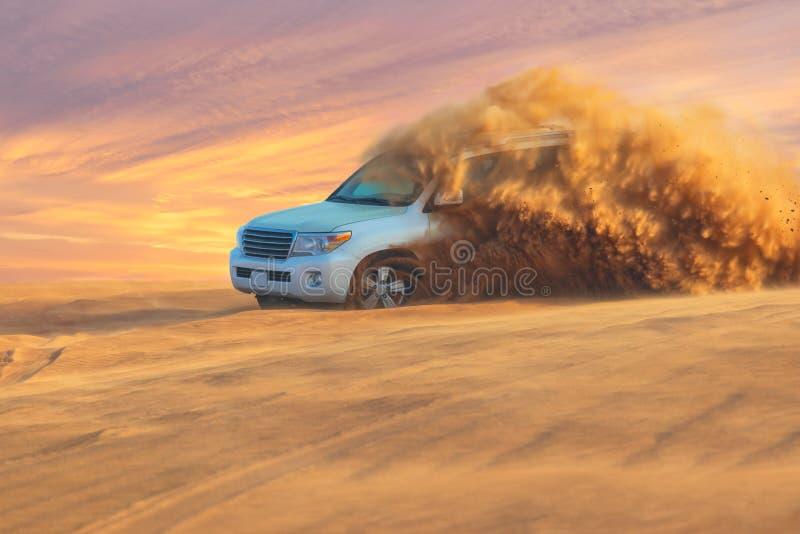 Aventura campo a través con SUV en desierto árabe en la puesta del sol Visita Dubai imagen de archivo