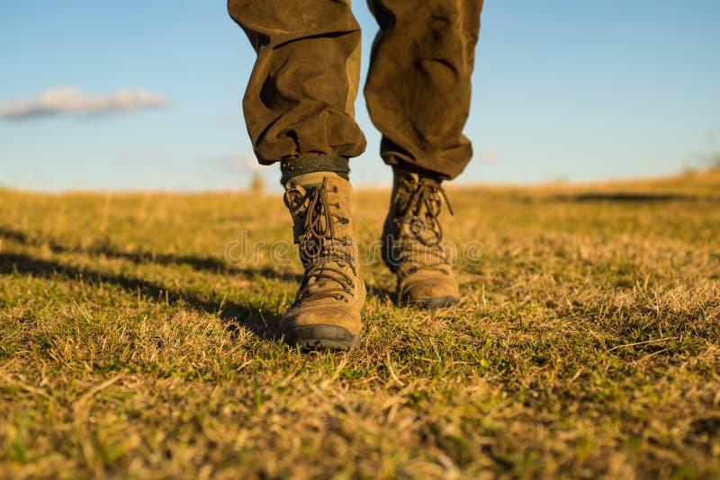 Aventura del viaje futuro Zapatos militares pies masculinos en botas verdes hynter que busca para la víctima en campo de hierba E foto de archivo libre de regalías