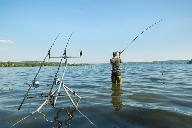 Aventuras de la pesca, pesca de la carpa El pescador está echando el cebo fotos de archivo