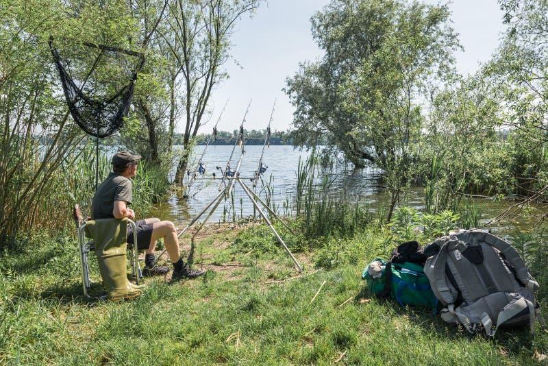 Aventuras de la pesca, pesca de la carpa Pescador con el equipo moderno imagen de archivo