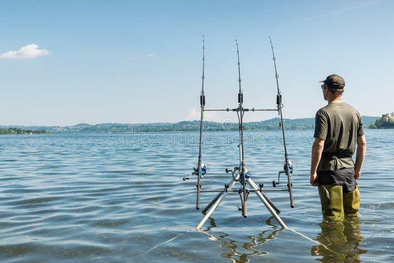 Aventuras de la pesca, pesca de la carpa Pescador con las botas de goma verdes imagenes de archivo