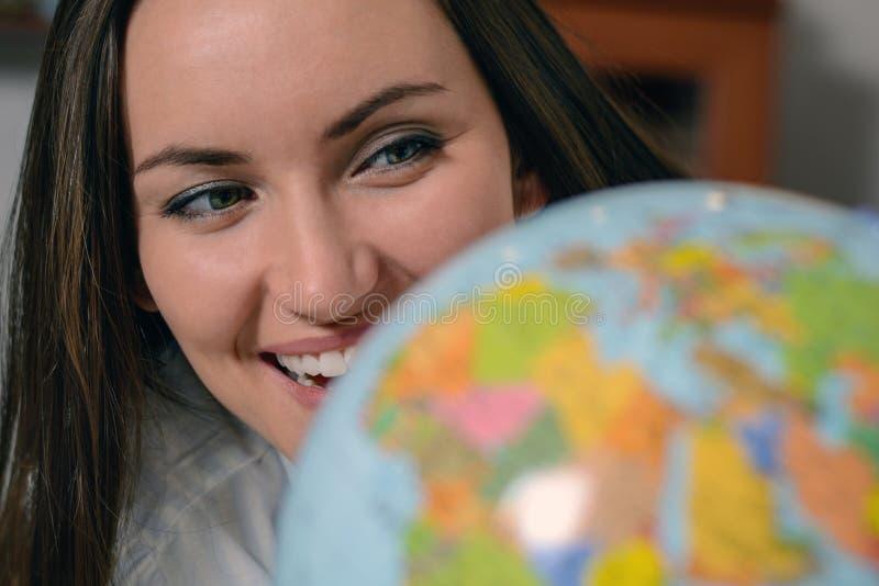 Aventuras ideales Mujer sonriente del primer en pijamas que mira el globo El concepto de planeamiento del viaje fotos de archivo