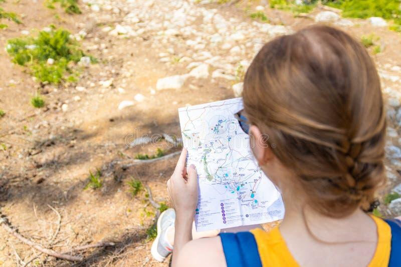 Aventure, concept de voyage La femme blonde de voyageur de touristes s'assied sur un rondin, regardant une carte et choisit l'iti photos stock