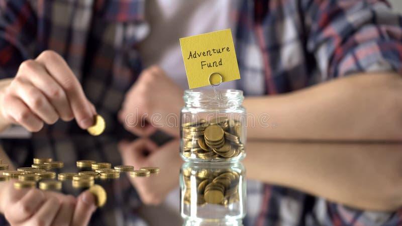 Aventure-se a frase acima do frasco do vidro com dinheiro, economias para o passatempo, interesses do fundo foto de stock royalty free
