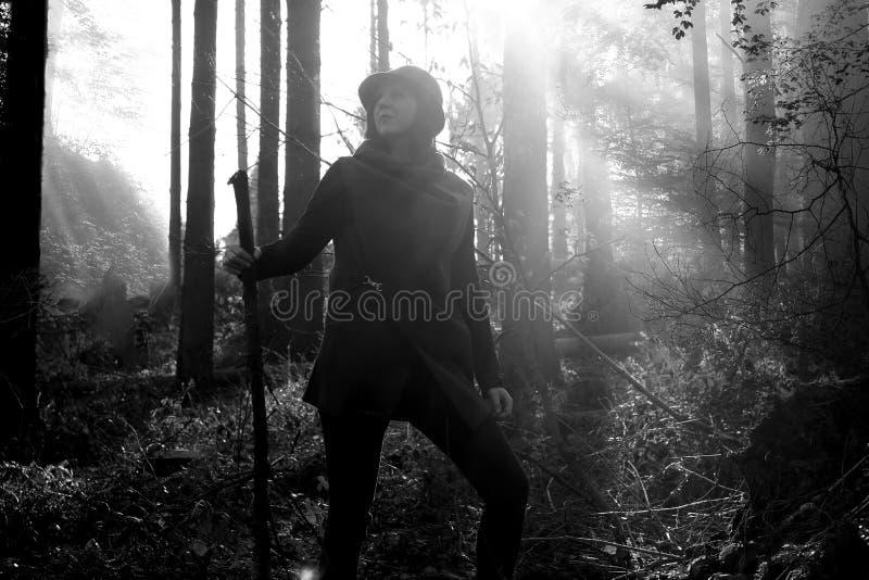 Aventure-se a mulher com uma haste de madeira em uma floresta foto de stock