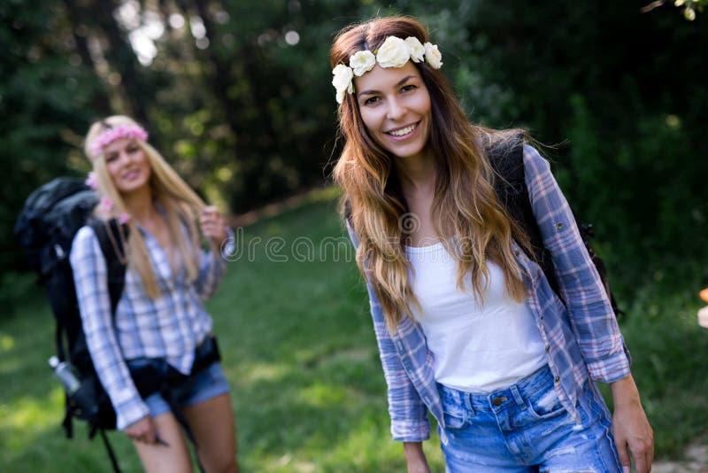 Aventure-se, viaje-se, turismo, caminhada e conceito dos povos Mulheres felizes com as trouxas na floresta fotografia de stock royalty free