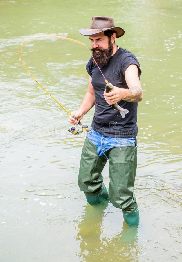 Aventures de pêche de baie Week-end d'?t? P?che de mouche dans les eaux calmes Pêcheur barbu heureux dans l'eau utilisation de te images stock