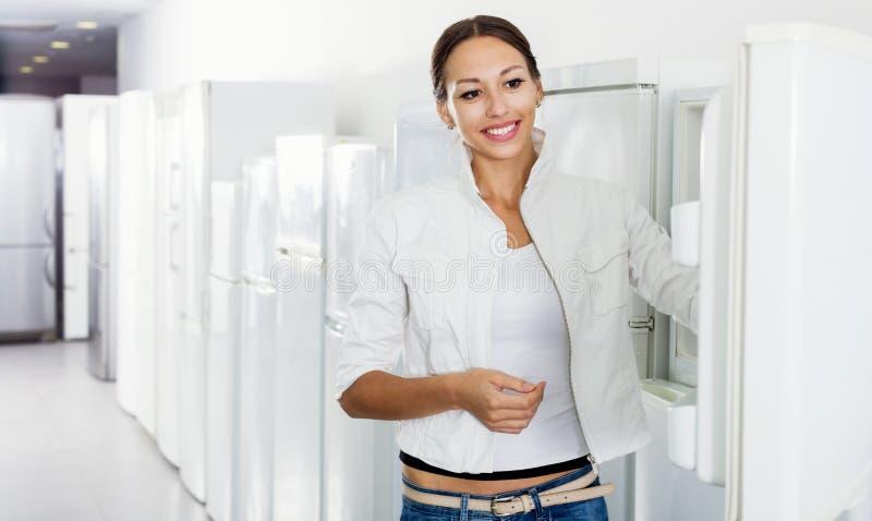 Average female customer looking at modern fridges stock photography