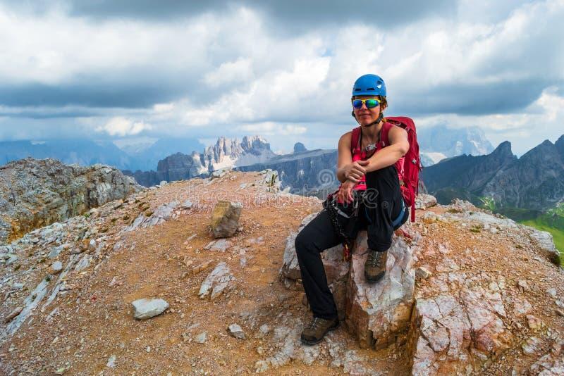 Averau峰顶的女性登山人在a结束时通过ferrata路线,当黑暗的暴风云接近在背景中 库存图片