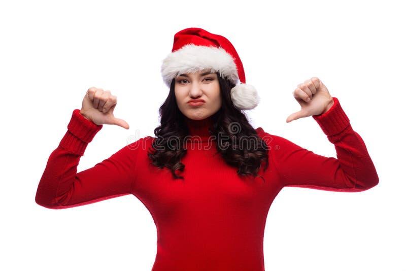 Aversión de la demostración del sombrero de la Navidad de la muchacha que lleva morena con los pulgares abajo, concepto del recha imagen de archivo