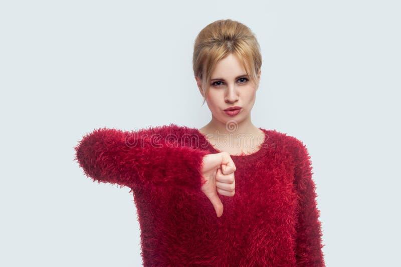 aversi?n Retrato de la mujer rubia joven hermosa triste descontenta en la situación roja de la blusa con los pulgares abajo y mir imagen de archivo libre de regalías