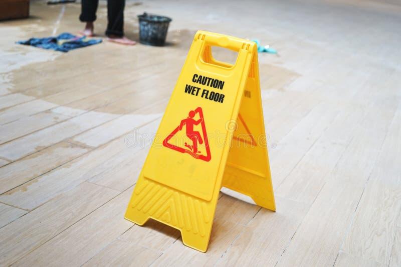 Avertissez le panneau d'avertissement humide de plancher avec le travailleur brouillé photographie stock
