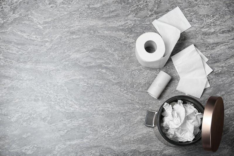 Avfallfack med använt toalettpapper och ny rulle på grå bakgrund, bästa sikt fotografering för bildbyråer