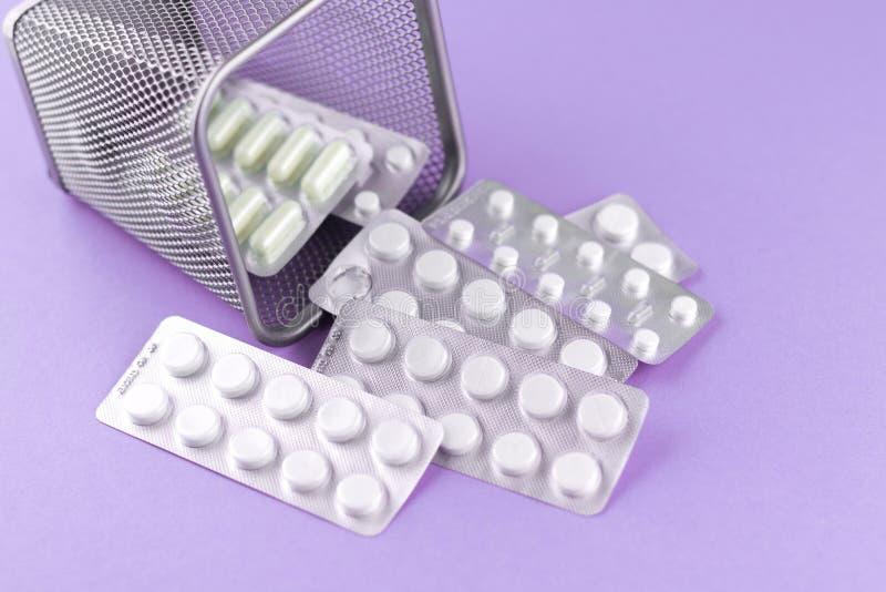 Avfallfacket med packar av vita kapslar och preventivpillerar packade i blåsor med kopieringsutrymme på purpurfärgad bakgrund Fok arkivbild