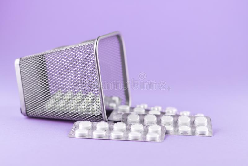 Avfallfacket med packar av vita kapslar och preventivpillerar packade i blåsor med kopieringsutrymme på purpurfärgad bakgrund Fok arkivbilder