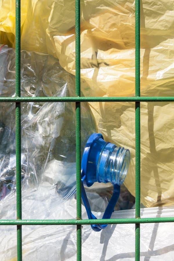 Avfallkorg med flaskan och plastpåsar. royaltyfria bilder