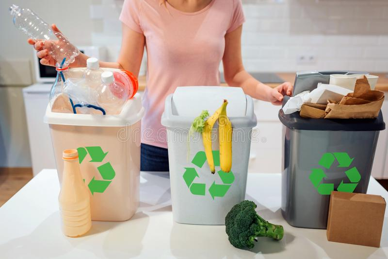 Avfalls som hemma sorterar återanvändning Kvinna som sätter den plast- flaskan i avskrädefacket i köket arkivbild
