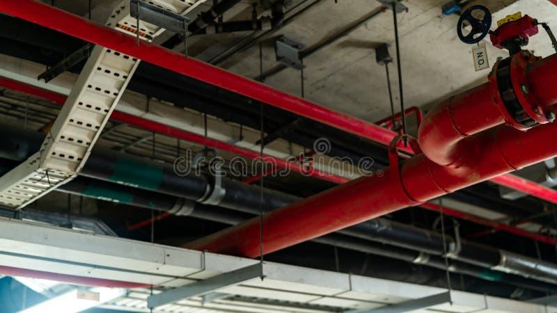 Avfyra sprinkleranläggningen med röda rör som hänger från tak inom byggnad Branddämpning Brandskydd och avkännare huvud royaltyfria foton