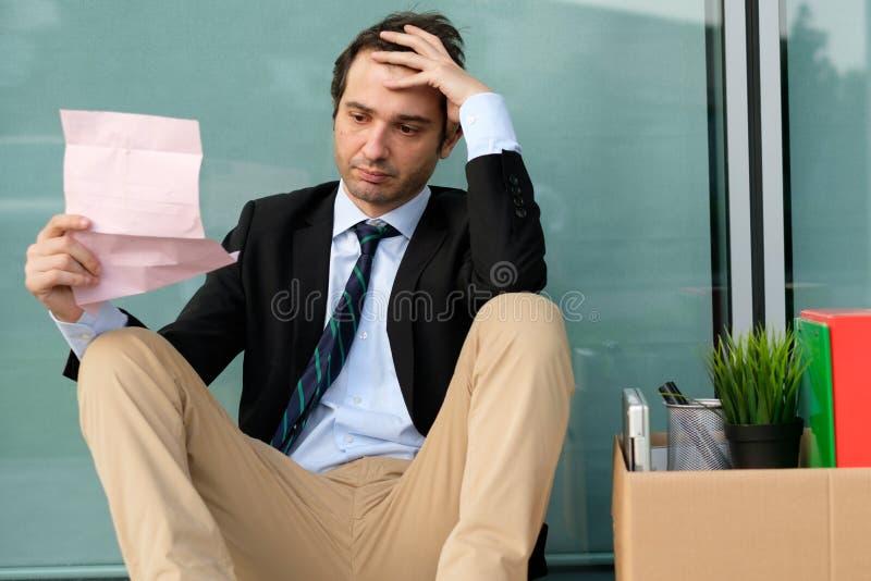 Avfyrad affärsman som utanför läser meddelandet av jobbavslutningen arkivfoton