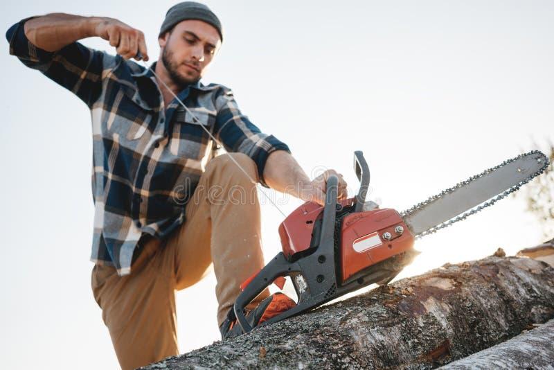 Avfyrar den bärande plädskjortan för den yrkesmässiga skogsarbetaren upp chainsawen på sågverket royaltyfria foton