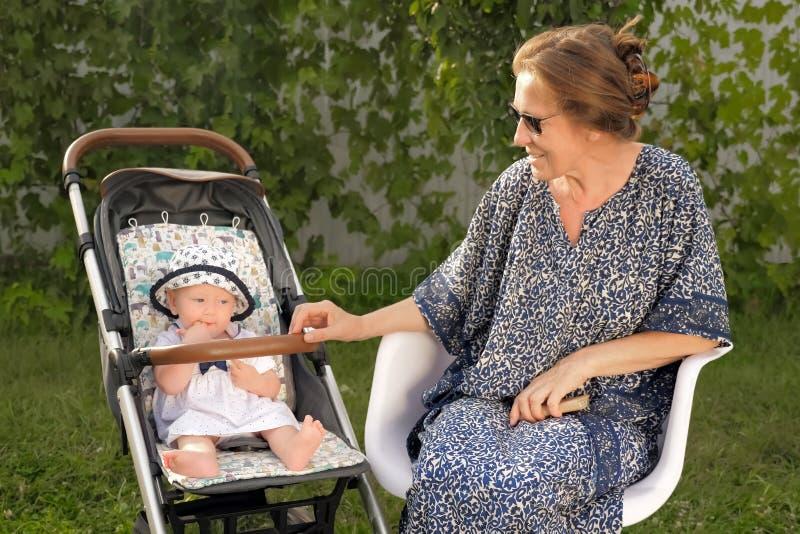 Avgångbakgrund lycklig begreppsfamilj Farmor med sondottern Familjunderhållning arkivbild