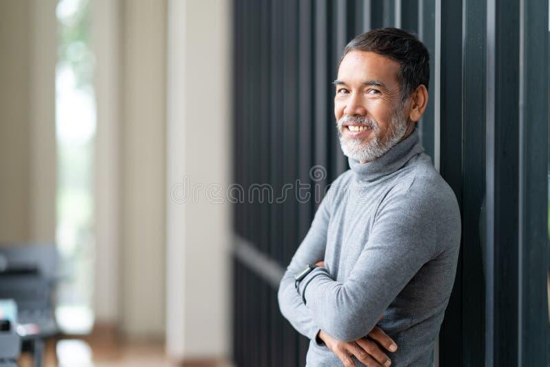 Avgick den attraktiva mogna asiatiska mannen för ståenden med det stilfulla korta skägget som ler på den utomhus- coffee shop arkivbild