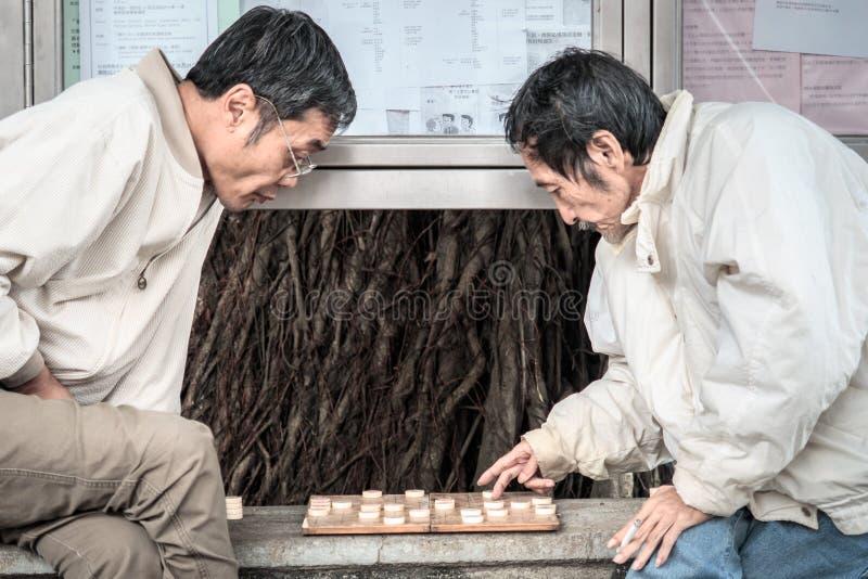 Avgick kinesiska gamala män spelar kinesiskt schack på gatan av Hong Kong arkivbild
