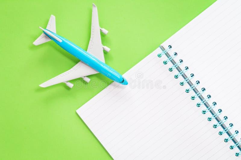Avião azul do brinquedo com um bloco de notas no fundo verde fotografia de stock