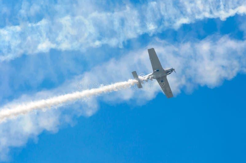 Avião branco da turboélice com um traço do fumo branco contra um céu azul imagens de stock