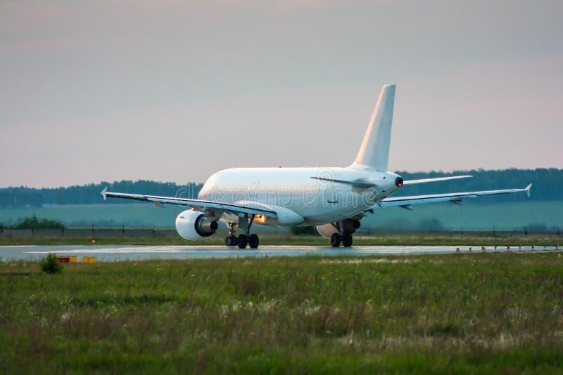 Avião branco do passageiro que taxiing à pista de decolagem imagens de stock