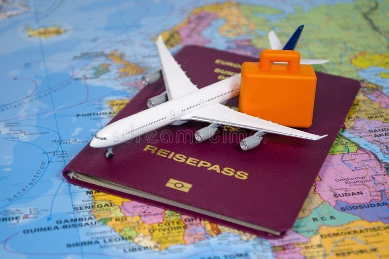 Avião com um passaporte alemão em um mapa do mundo foto de stock royalty free