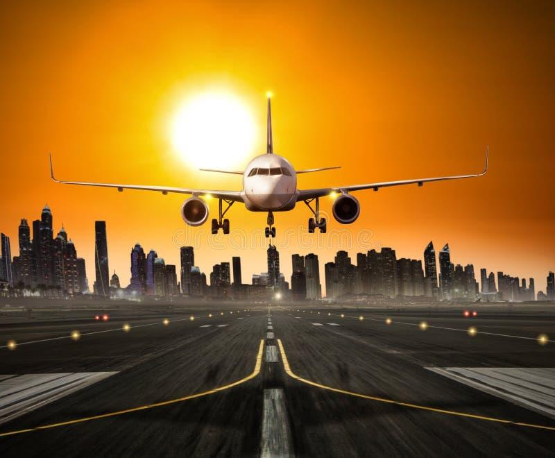 Avião comercial de aterrissagem na pista de decolagem, cidade moderna no fundo fotos de stock
