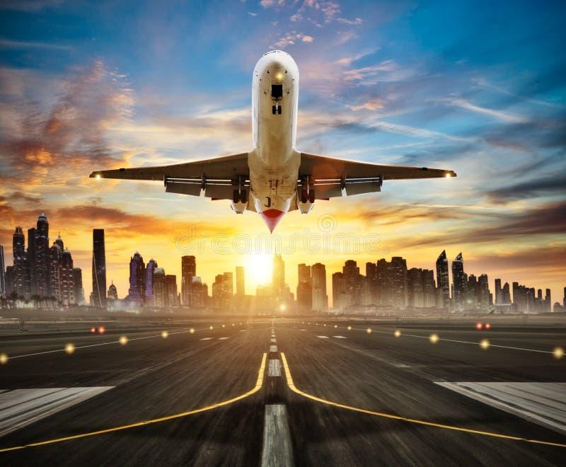 Avião comercial de aterrissagem na pista de decolagem, cidade moderna no fundo fotografia de stock royalty free