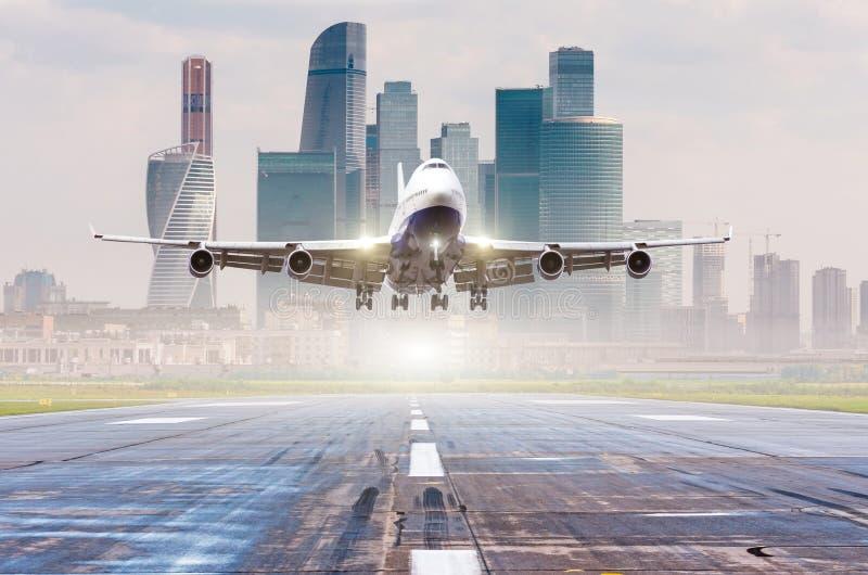 Avião comercial do avião que aproxima-se para aterrar na pista de decolagem, cidade moderna no fundo foto de stock